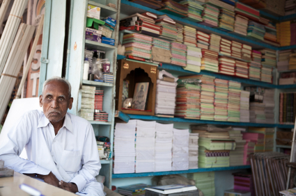 Senior Indian man sitting is his bookshop