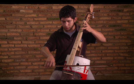 'Bebi' plays a cello made of recycled parts © Landfill Harmonic http://www.landfillharmonicmovie.com/