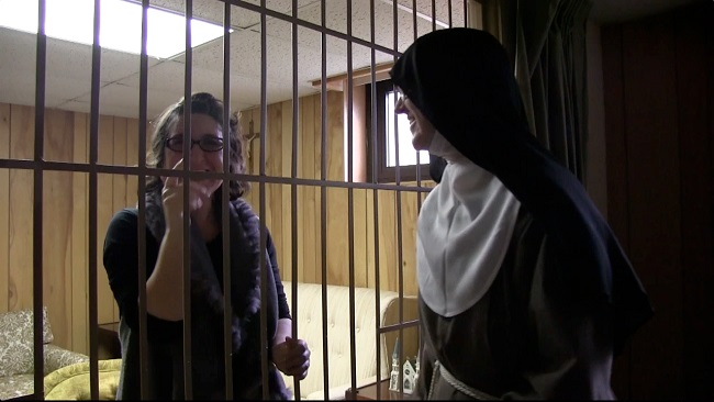 A metal grille is the literal and symbolic separation and reflection of the nuns' vow of enclosure. The Poor Clare Colettine nuns film Abbie Reese, in this screenshot, for a collaborative ethnographic documentary film in-progress by Abbie and the nuns. Courtesy of Abbie Reese.