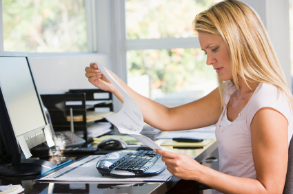 Woman in home office with computer and paperwork frowning. © monkeybusinessimages via iStockphoto.
