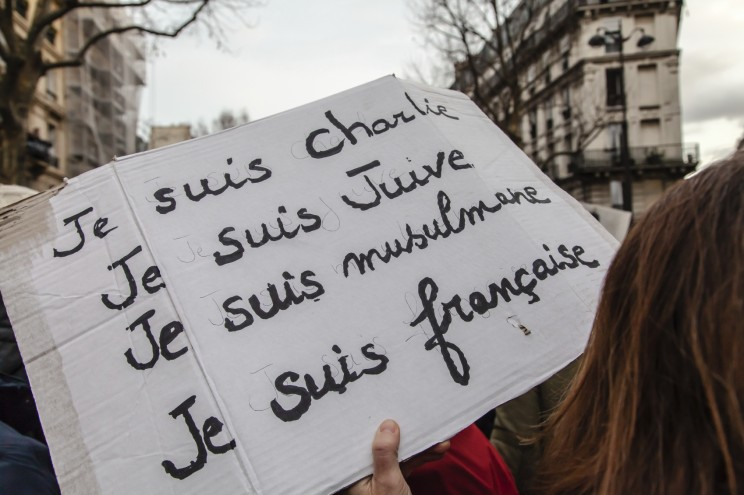 """Paris, France - January 11, 2015: Woman with banner reading in french """"I am Charlie I am Jewish I am muslim I am french"""" during the anti-terrorism rally in Paris. © Guillaume Louyot - Onickz Artworks via iStock."""