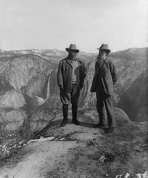 U.S. President Theodore Roosevelt (left) and nature preservationist John Muir, founder of the Sierra Club, on Glacier Point in Yosemite National Park. In the background: Upper and lower Yosemite Falls. Public Domain via Wikimedia Commons.