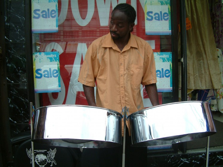 A steelpan player on High Street in Trinidad and Tobago. Photo by Shanel. CC by-SA 3.0 via Wikimedia Commons.