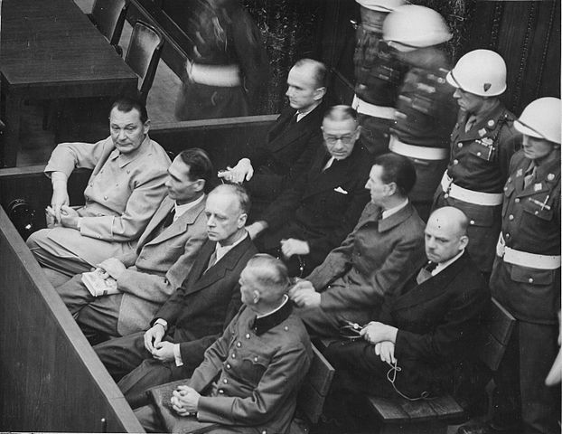 Nuremberg Trials. Defendants in their dock, circa 1945-1946. Work of the United States Government. Public domain via Wikimedia Commons.