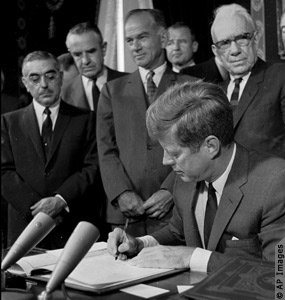 President John F. Kennedy signs the Limited Test Ban Treaty in October 1963.