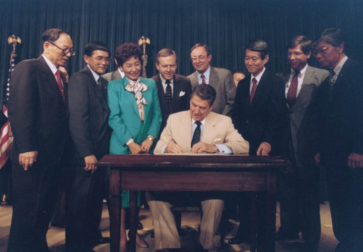 President Ronald Reagan signing the Japanese reparations bill.