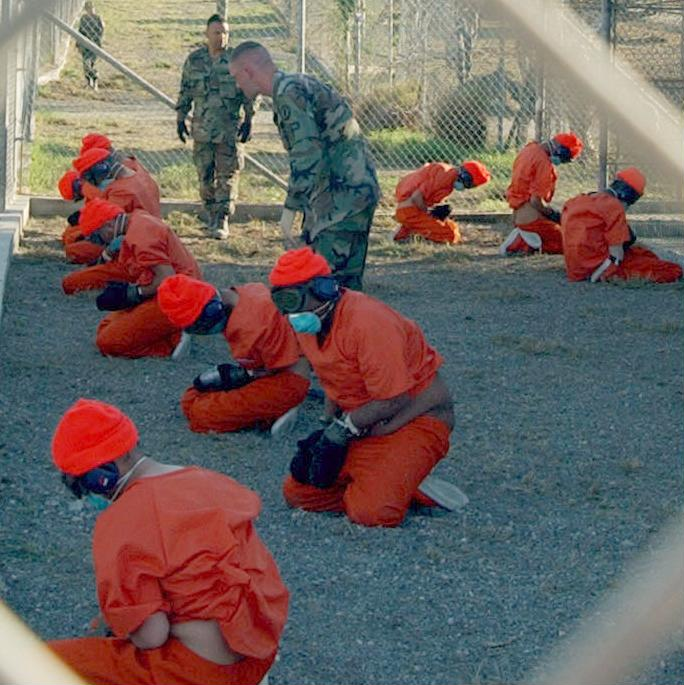 Detainees in orange jumpsuits sit in a holding area under the watchful eyes of Military Police at Camp X-Ray at Naval Base Guantanamo Bay, Cuba, during in-processing to the temporary detention facility on Jan. 11, 2002. The detainees will be given a basic physical exam by a doctor, to include a chest x-ray and blood samples drawn to assess their health. DoD photo by Petty Officer 1st class Shane T. McCoy, U.S. Navy.
