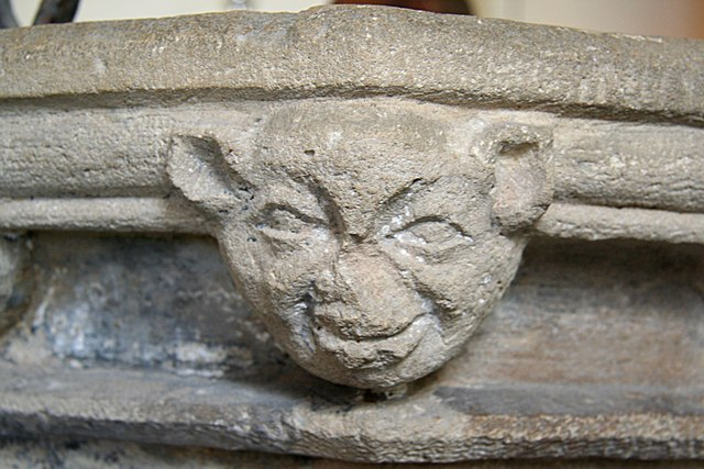 An authentic cluck-ma-doodle. (An impish face carved on St. Mary's 14th century font, Knaith. Photo by Richard Croft. CC BY-SA 2.0 via Wikimedia Commons)