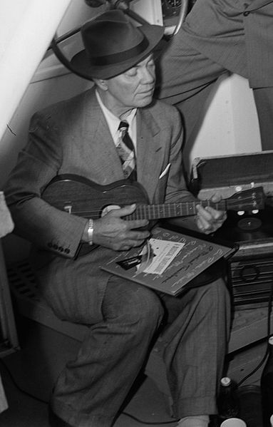 Cliff Edwards playing ukulele with phonograph, 1947. Photography from the William P. Gottlieb Collection. Public domain via Wikimedia Commons.