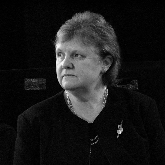 The head and shoulders of Janet Finch, pictured on the platform as a guest speaker at the 11 November 2003 General Meeting of the Keele University Students' Union. KUSU Ballroom, Keele, Staffordshire, UK. Public domain via Wikimedia Commons.