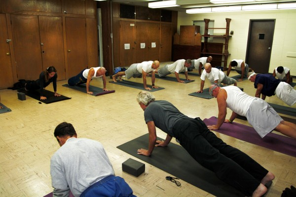 Founder and Director of the Prison Yoga Project James Fox leads students through the uttihita chaturanga danda asana (plank posture) in 2012 at San Quentin State Prison in San Quentin, California. Photographed by Robert Sturman. (Courtesy of Robert Sturman.)