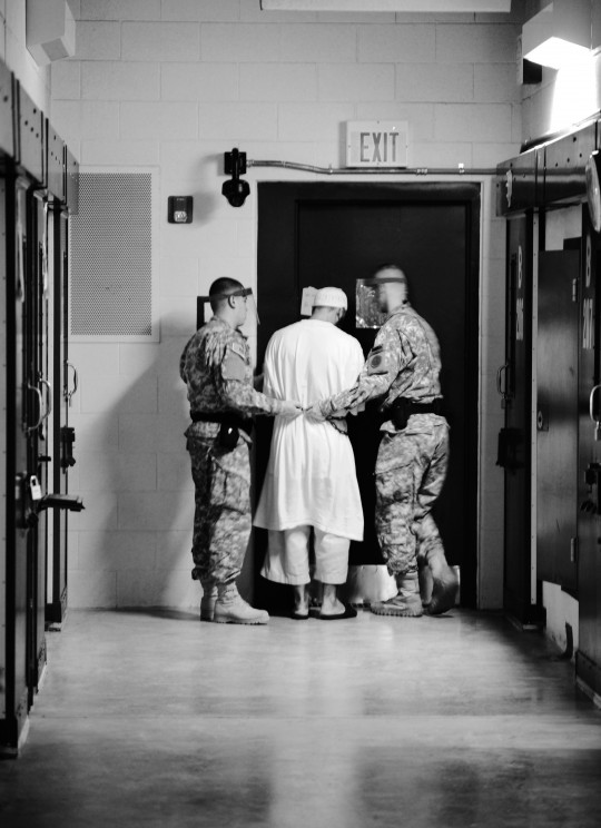 Guards from Camp 5 at Joint Task Force Guantanamo escort a detainee from his cell to a recreational facility within the camp.