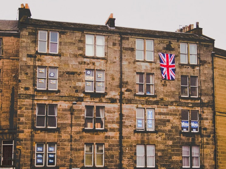 Tenement block in Leith (North Junction Street/Lindsay Road junction), with both YES and NO referendum posters and Union flag. By Brian McNeil CC-BY-SA-3.0 via Wikimedia Commons.