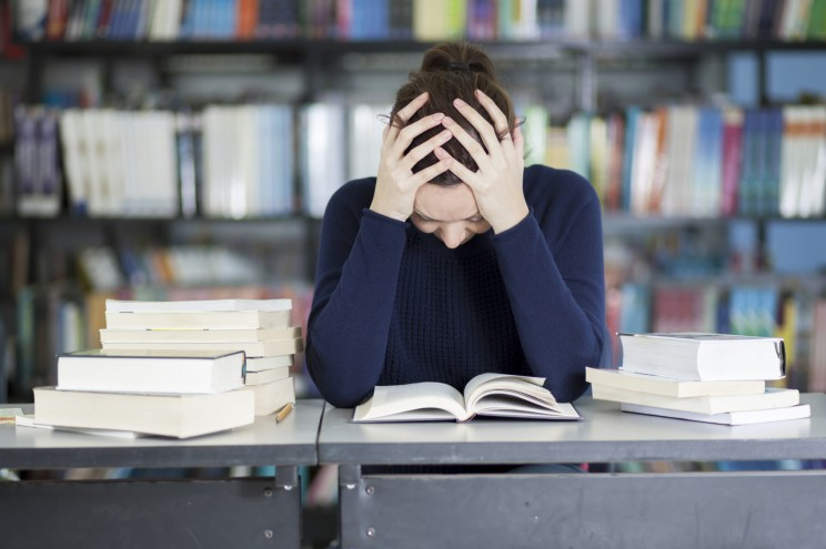 Female college student stressed and overwhelmed and trying to study at the school library. © Antonio_Diaz via iStock.