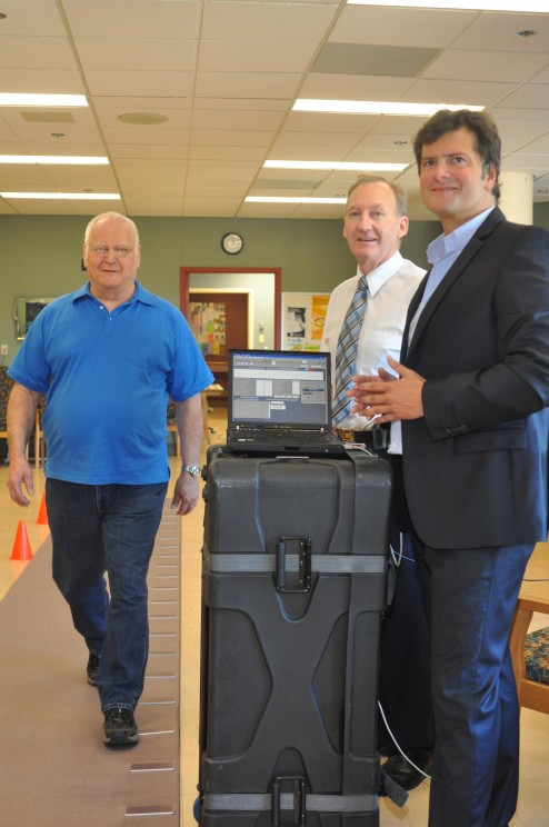 Drs. Michael Borrie (middle) and Manuel Montero-Odasso (right) performing a gait assessment of the data about gait speed and variability.