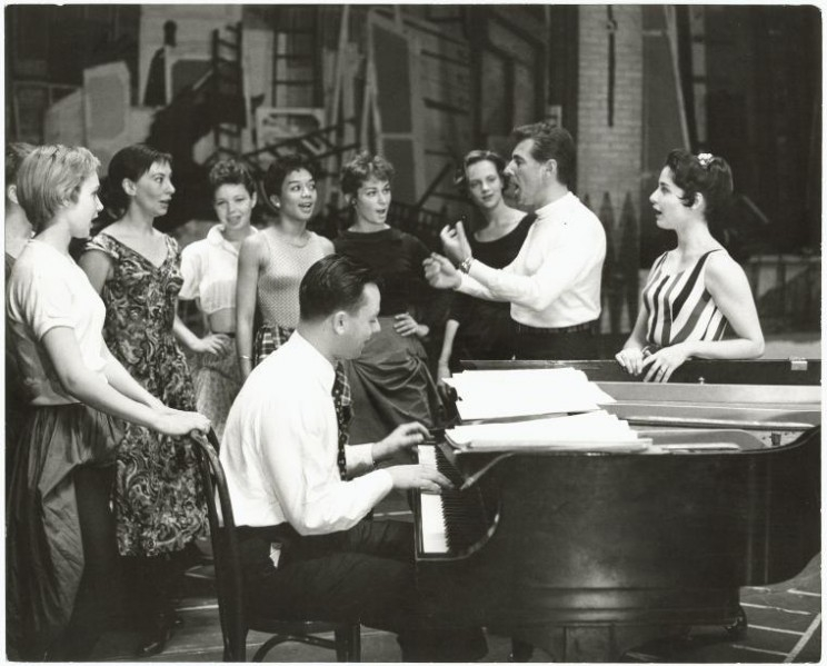 Stephen Sondheim on piano with Leonard Bernstein and Carol Lawrence (on far right) standing amongst female singers rehearsing for the stage production West Side Story. NYPL Digital Collections.