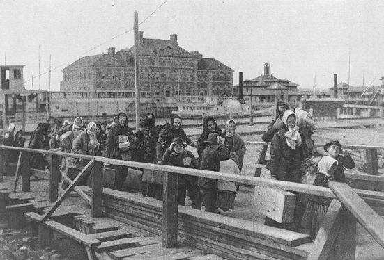 Emigrants coming up the board-walk from the barge, which has taken them off the steamship company's docks, and transported them to Ellis Island. Public domain via the Library of Congress.