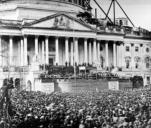 Abraham Lincoln's first inauguration which took place in Washington, DC. Lincoln stands underneath the covering at the center of the photograph. The scaffolding at upper right was being used in construction of the Capitol dome.