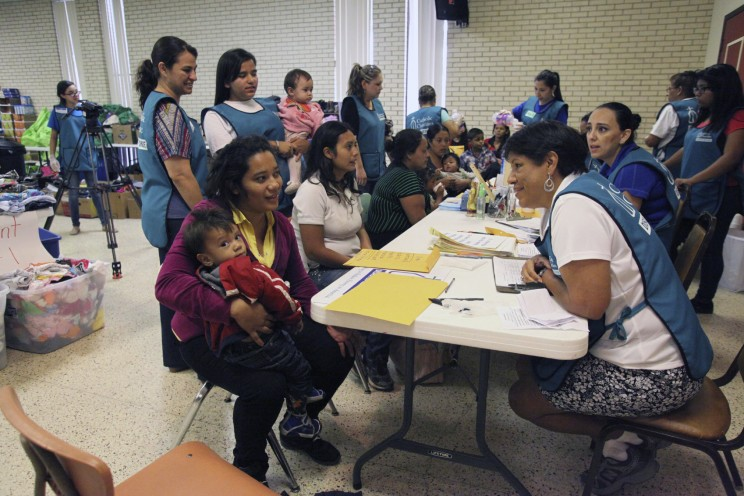McAllen, TX, USA - July 8, 2014: A volunteer member of a Catholic Charities Disaster Response Team talks with a Central American refugee mother and child at the intake and orientation table of the reception hall of the Sacred Heart Catholic Church. Although volunteers came from various churches and denominations, Sacred Heart was the epicenter of the McAllen refugee assistance effort. (c) vichinterlang via iStock.