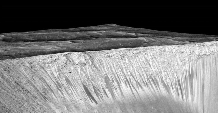 Signs of water? Perspective view of dark narrow streaks (recurring slope lineae) a few hundred metres long on the wall of Garni crater on Mars. Image Credit: NASA/JPL-Caltech/Univ. of Arizona