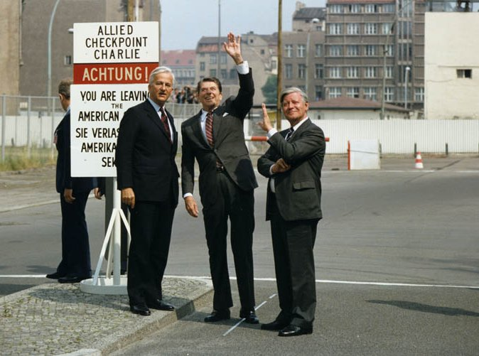 Photograph of Berlin Mayor Richard von Weizsaecker, President Reagan, and Chancellor Helmut Schmidt at Checkpoint Charlie at the Berlin Wall, November 1982. Public domain courtesy Ronald Reagan Library via Wikimedia Commons.