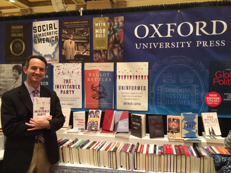 """Seth Masket takes a minute at our OUP booth to take a picture with """"The Inevitable Party"""""""