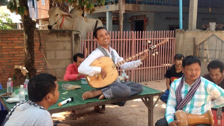 "Pich Sarath plays and sings traditional instrument/genre ""chapei"" on a rural village tour of the ""Khmer Magic Music Bus"", 28 October 2015. Photo by the author."