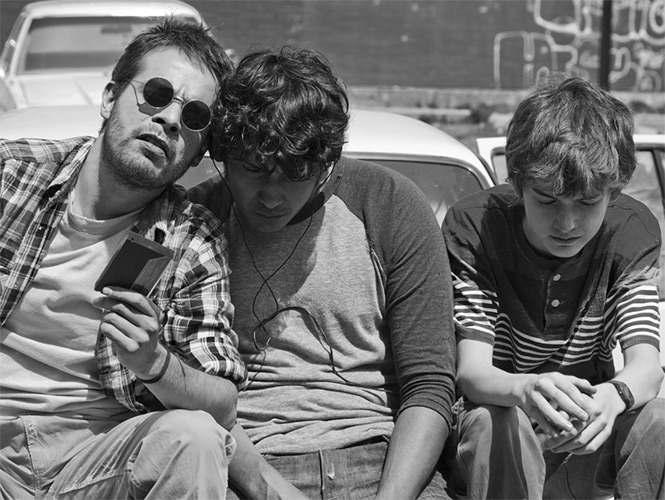 Publicity still of three boys sharing headphones