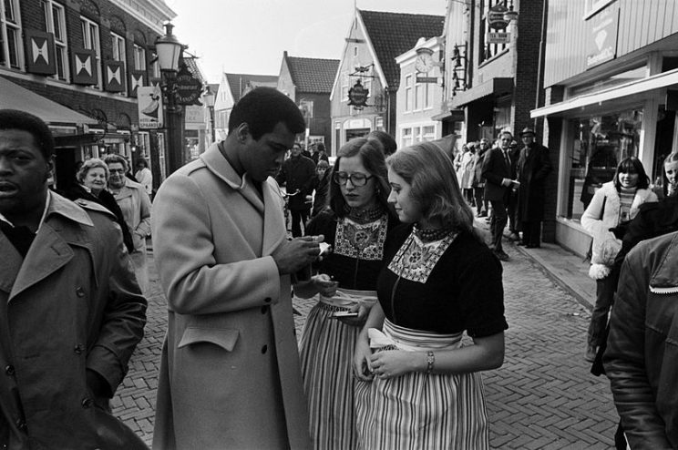 Muhammad Ali signing autographs for Volendam girls. Nationaal Archief, March 1976, Netherlands. CC SA 3.0 Netherlands via Wikimedia Commons.