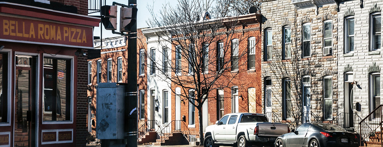 Baltimore, Maryland, USA - December 20, 2016: View to the streets of West Baltimore, typical row houses and a pizza place.