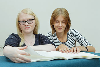 Photo of two women reading Braille literature