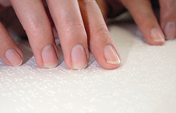 Photo of person's hands reading Braille literature